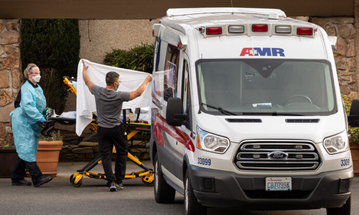 Healthcare workers transport a patient on a stretcher into an ambulance at Life Care Center of Kirkland in Kirkland, Washington on Feb. 29, 2020. (David Ryder/Getty Images)
