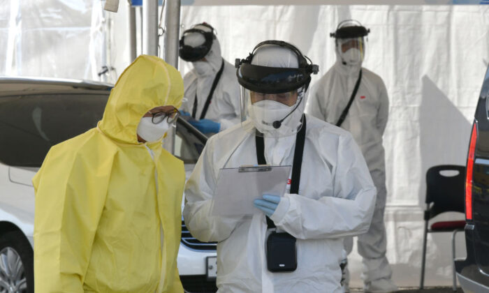 """Medical members wearing protective gear talk as they check drivers with suspected symptoms of the novel coronavirus, at a """"drive-through"""" virus test facility in Goyang, South Korea, on Feb. 29, 2020. (Jung Yeon-je/AFP via Getty Images)"""