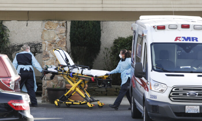 A stretcher is moved from an AMR ambulance to the Life Care Center of Kirkland, where one associate and one resident were diagnosed with COVID-19, according to a statement released by the facility in Kirkland, Washington, on Feb. 29, 2020. (Jason Redmond/AFP via Getty Images)