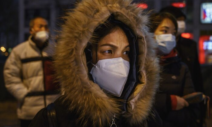 Chinese office workers wear protective masks as they line up for the bus after work in Beijing on March 2, 2020. (Kevin Frayer/Getty Images)