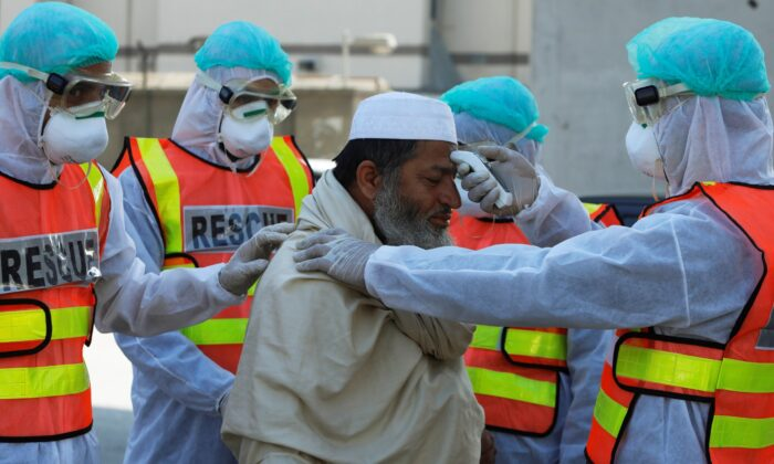 Rescue workers wearing masks and protective clothing check a man's temperature during a mock drill on handling suspected carriers of coronavirus, in Peshawar, Pakistan, on March 2, 2020. (Fayaz Aziz/Reuters)