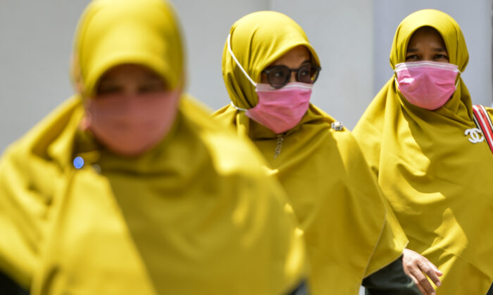 Women wearing face masks walk in a public area in Banda Aceh, Indonesia, on March 2, 2020. (Chaideer Mahyuddin/AFP/Getty Images)