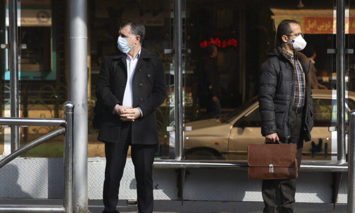 Men wearing face masks wait for a bus in northern Tehran, Iran, on March 1, 2020. (Vahid Salemi/AP Photo)