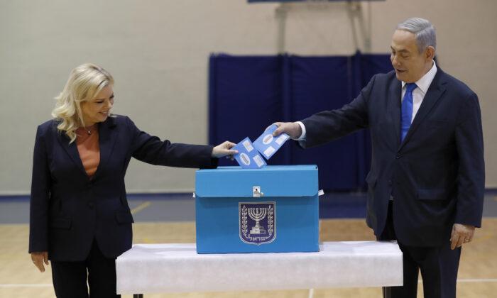 Israeli Prime Minister Benjamin Netanyahu, (R), and his wife Sara Netanyahu cast their ballots during the Israeli legislative elections at a polling station in Jerusalem, Israel, on March 2, 2020. (Atef Safadi/Pool Photo via AP)