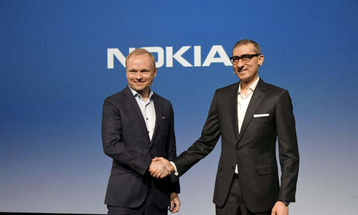 Nokia's new President and CEO Pekka Lundmark shakes hands with resigning President and CEO Rajeev Suri (R) after a news conference at the Nokia headquarters in Espoo, Finland, on March 2, 2020. (Lehtikuva/Markku Ulander via Reuters)