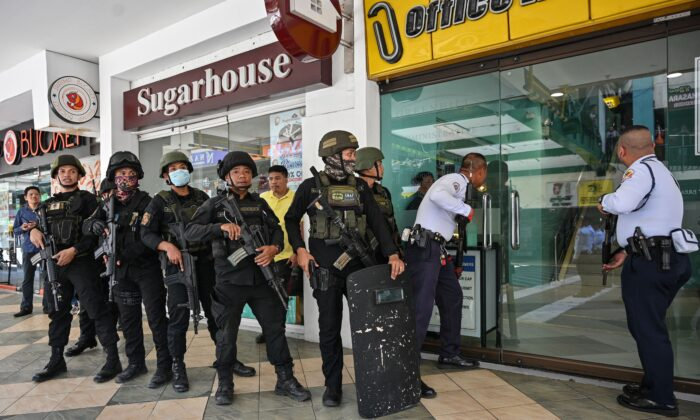 Members of a police SWAT team prepare to enter a mall after a hostage situation was reported in suburban Manila on March 2, 2020. (Photo by Ted Aljibe/AFP/Getty Images)