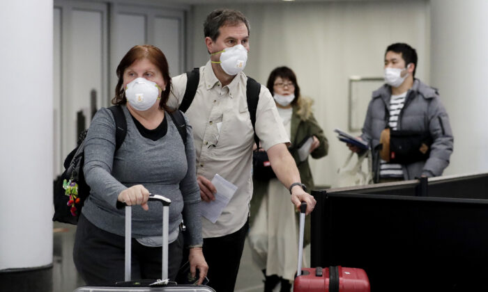 Travelers wear protective masks as they walk through terminal 5 at O'Hare International Airport in Chicago on March 1, 2020. (Nam Y. Huh/AP Photo)