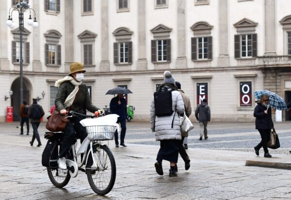 A woman wearing a protective mask crosses Piazza Duomo with her bicycle in Milan