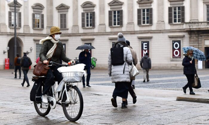 A woman wearing a protective mask crosses Piazza Duomo with her bicycle in Milan on March 2, 2020. (Miguel Medina/AFP via Getty Images)
