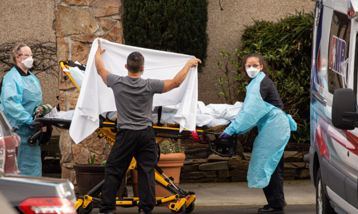 A worker shields a patient on a stretcher being taken to an ambulance at the Life Care Center of Kirkland in Washington state on Feb. 29, 2020. (David Ryder/Getty Images)