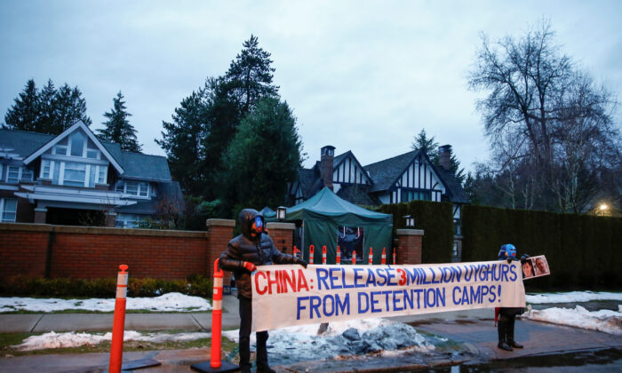 Protesters hold a large sign against China's Uyghur camps, labeled as vocational training centers by the Chinese regime, outside the home of Huawei Chief Financial Officer Meng Wanzhou before her extradition hearing at B.C. Supreme Court in Vancouver, British Columbia, Canada, on Jan. 20, 2020. (Lindsey Wasson/Reuters)