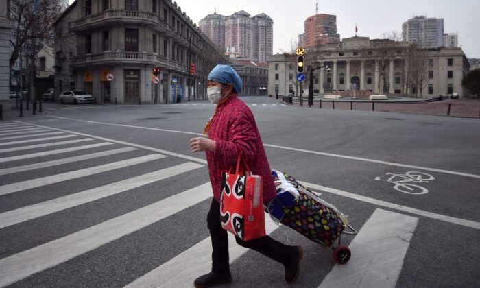 A woman crosses an empty street in Wuhan, the epicentre of the coronavirus outbreak in China, on Feb. 21, 2020. (Chinatopix via AP)