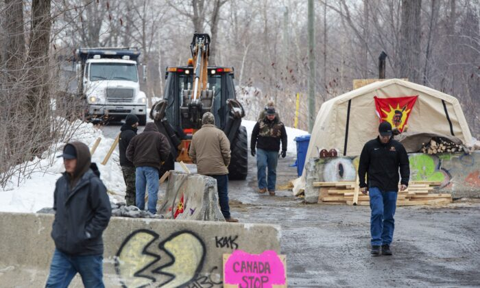Members of the Mohawk community dump more gravel at the entrance to the blockade of the commuter rail line in Kahnawake, Que., on Feb. 26, 2020. (The Canadian Press/Ryan Remiorz)