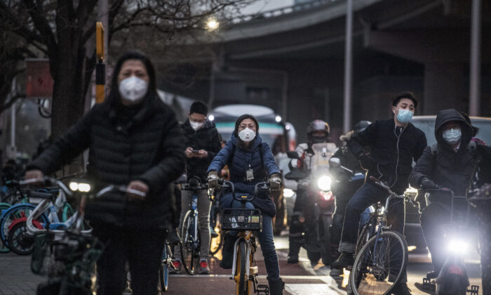 Chinese commuters on bikes wear protective masks while waiting for a light to change after leaving work on March 2, 2020 in Beijing, China. (Kevin Frayer/Getty Images)