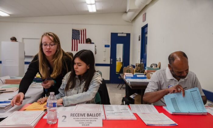 Volunteers Julian Shelby (R), Brittney Duran (C), and Natalie King assist voters at the Golden Hill Recreation Center, a polling place for the primary in San Diego on March 3, 2020. (Ariana Drehsler/AFP via Getty Images)