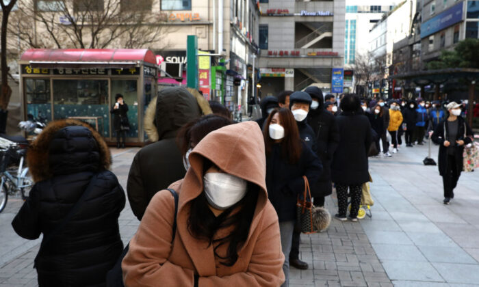 People wearing masks line up to buy face masks at a department store in Seoul on March 2, 2020. (Chung Sung-Jun/Getty Images)