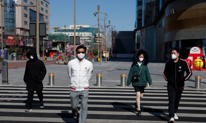 People wearing masks walk in a shopping street in Beijing, as the country is hit by an outbreak of the novel coronavirus, China, on March 3, 2020. (Thomas Peter/Reuters)