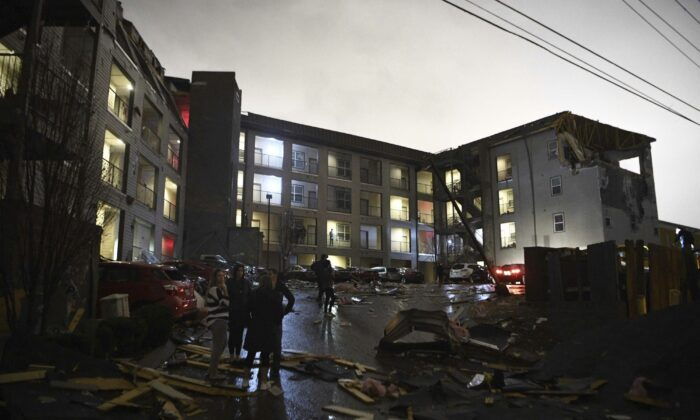 Debris is scattered across the parking lot of a damaged apartment building after a tornado hit Nashville in the early morning hours of March 3, 2020. (Courtney Pedroza/The Tennessean via AP)