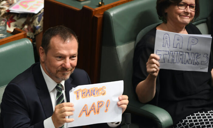 The Australian Associated Press has announced it will be shutting down after 85 years. Labor ministers hold up 'Thanks AAP' signs during Question Time in the House of Representatives in Canberra, Australia on March 03, 2020. (Tracey Nearmy/Getty Images)
