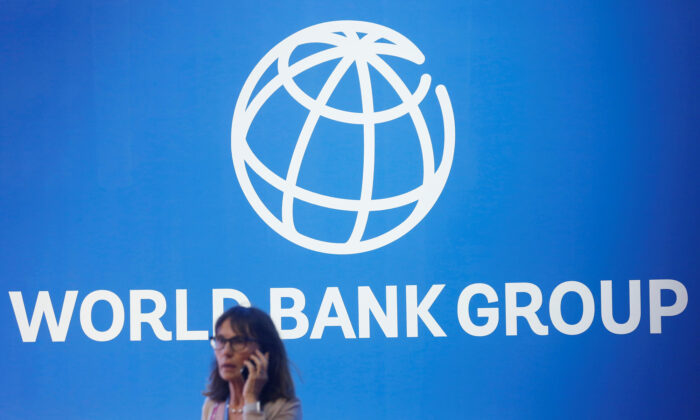 A woman stands near a logo of World Bank in Bali, Indonesia, on Oct. 12, 2018. (Johannes P. Christo/Reuters)