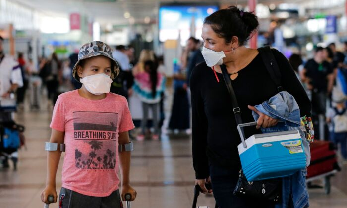 Passengers walk with protective masks at the Arturo Merino Benitez International Airport, in Santiago, on March 3, 2020. (Javier Torres/AFP via Getty Images)