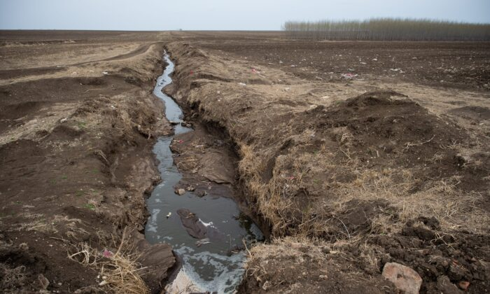 A pipe releases waste water into fields surrounding a dairy farm (not pictured) in Gannan County, Heilongjiang Province, China, on May 3, 2016. (Nicolas Asfouri/AFP via Getty Images)