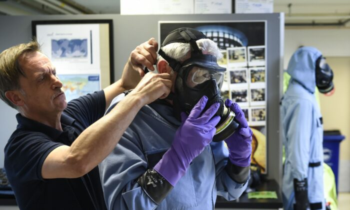 A man tries on an air permeable charcoal impregnated suit, combined with a respirator (or gas mask), rubber boots and three layers of gloves during a simulation at the OPCW (The Organisation for the Prohibition of Chemical Weapons) headquarters in The Hague, The Netherlands, on April 20, 2017. (John Thys/AFP via Getty Images)