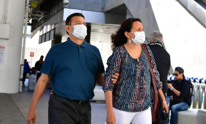 People wear face masks at Los Angeles International Airport (LAX) on March 2, 2020. (Frederic J. Brown/AFP via Getty Images)