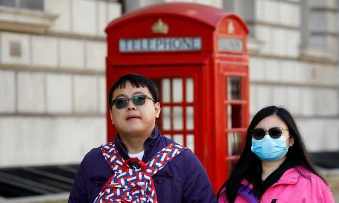 A tourist wears a surgical face mask as she walks past a red telephone box in central London on March 2, 2020. (Tolga Akmen/AFP via Getty Images)