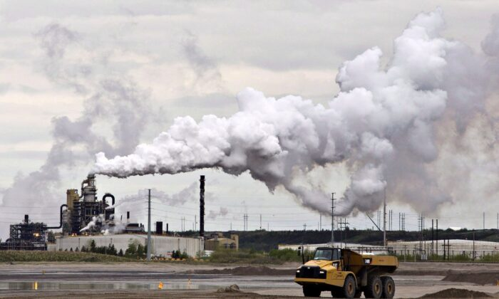 A dump truck works near the Syncrude oilsands extraction facility near Fort McMurray, Alberta, in a file photo. A constitutional expert says the provinces fighting the federal carbon tax have a good chance of winning. (The Canadian Press/Jason Franson)