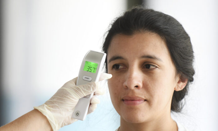 A nurse checks a passenger's body temperature as a preventive measure against the new coronavirus, COVID-19, at the Aurora International Airport, in Guatemala City, on March 4, 2020. (Johan Ordonez/AFP via Getty Images)