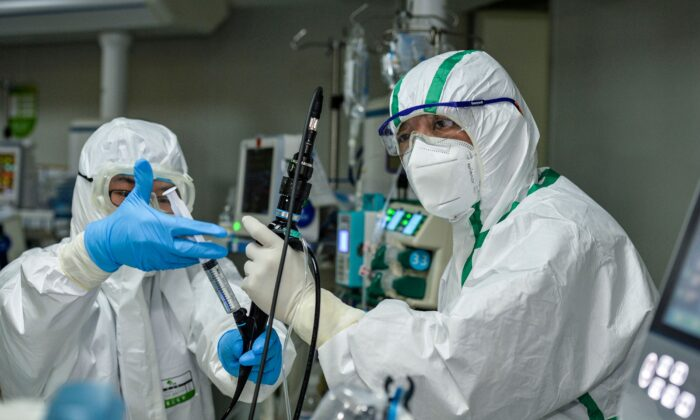 A doctor treats a patient infected by the COVID-19 coronavirus at a hospital in Wuhan in China's central Hubei province, on Feb. 24, 2020. (STR/AFP via Getty Images)