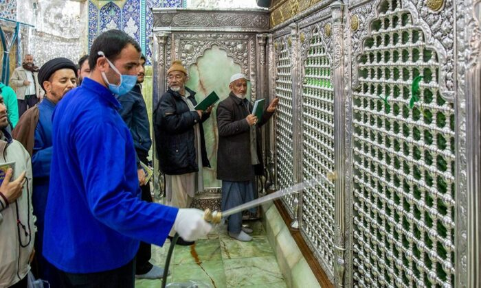 A man disinfects the shrine of Saint Masoumeh against coronavirus in the city of Qom 78 miles south of the capital Tehran, Iran on Feb. 24, 2020. (Ahmad Zohrabi/ISNA via AP)