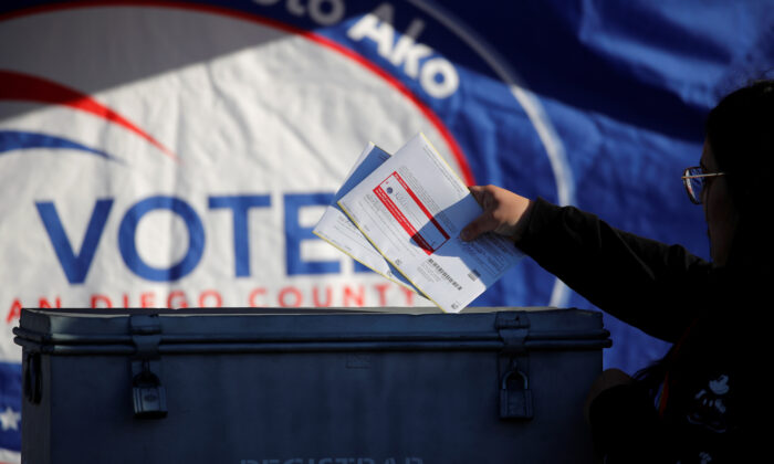 A poll worker drops ballots into a ballot box during the California primary in San Diego, Calif., on March 3, 2020. (Mike Blake/Reuters)