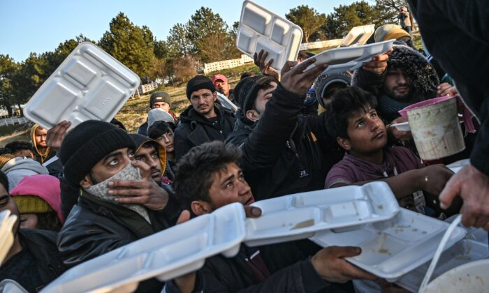 Migrants wait to be served food near the city of Edirne, northwestern Turkey, as they wait to cross the Meritsa river by boat and enter neighbouring Greece on March 2, 2020. (Ozan Kose/AFP via Getty Images)