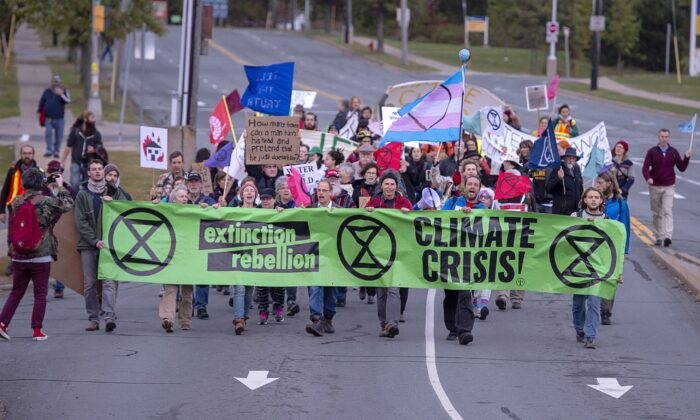 Extinction Rebellion climate activists march to the Angus L. Macdonald Bridge in Dartmouth, N.S., on Oct. 7, 2019, to block the bridge during the early morning rush hour as part of a string of protests in other Canadian cities. (The Canadian Press/Andrew Vaughan)