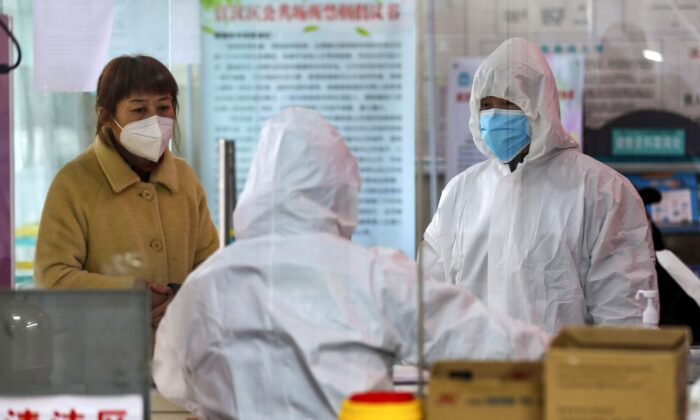 Medical workers in protective gear talk with a woman suspected of being ill with coronavirus at a community health station in Wuhan in central China's Hubei Province on Jan. 27, 2020. (Chinatopix via AP)