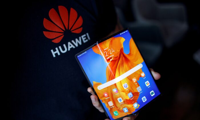 An employee displays the Huawei Mate Xs to the media during a photocall for the launch of the new foldable smartphone in London on Feb. 18, 2020. (TOLGA AKMEN/AFP via Getty Images)