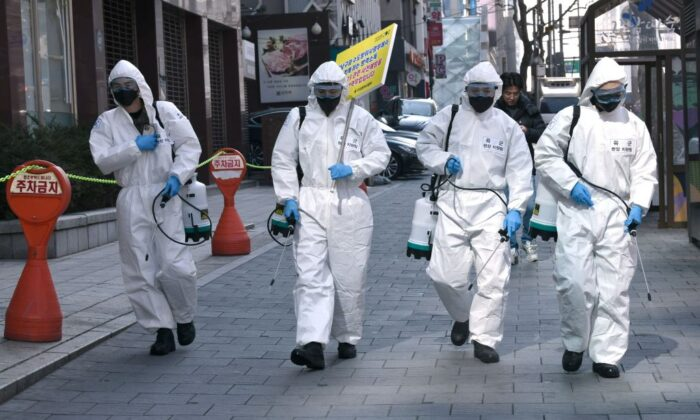 South Korean soldiers wearing protective gear spray disinfectant on the street to help prevent the spread of the novel coronavirus, at Gangnam district in Seoul on March 5, 2020. (Jung Yeon-je/AFP via Getty Images)