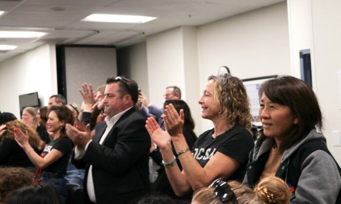 Attendees at the Orange County Board of Education meeting applaud the board's decision to renew the license of Orange County School of the Arts and take over as the school's authorizer, on March 4, 2020. (Jamie Joseph/The Epoch Times)
