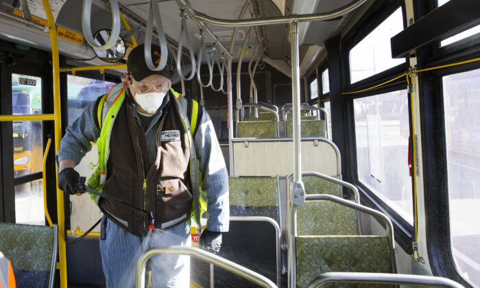 A King County Metro worker sprays a disinfectant on a metro bus in Seattle, Washington, on March 4, 2020. (Karen Ducey/Getty Images)