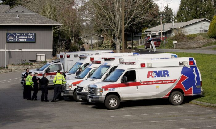 Ambulances are seen in a staging area at the North Kirkland Community Center, which is a short drive from the Life Care Center of Kirkland, the long-term care facility linked to several confirmed coronavirus cases in the state, in Kirkland, Wash., on March 4, 2020. (David Ryder/Reuters)