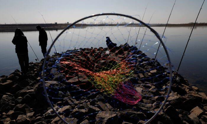 Chinese men fish as watchtowers are seen on the North Korean side of the Yalu River just north of Dandong, in China's Liaoning Province, on Nov. 20, 2017. (Damir Sagolj/Reuters)