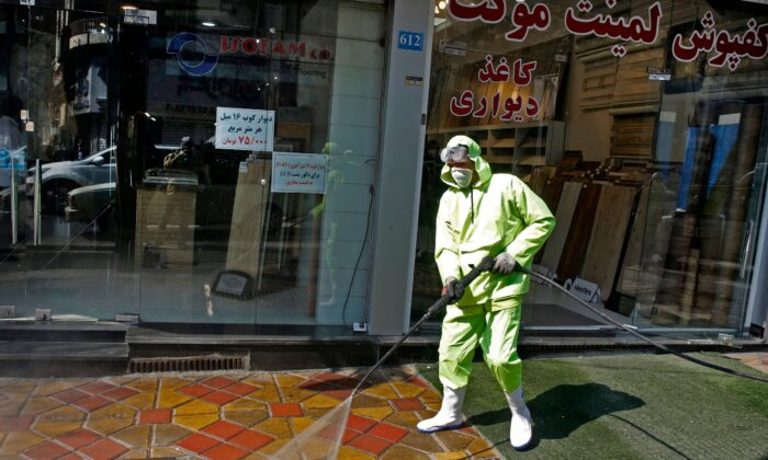 Iranian fire fighters and municipality workers disinfect a street in the capital Tehran for corona virus COVID-19 on March 5, 2020. (Stringer/AFP via Getty Images)