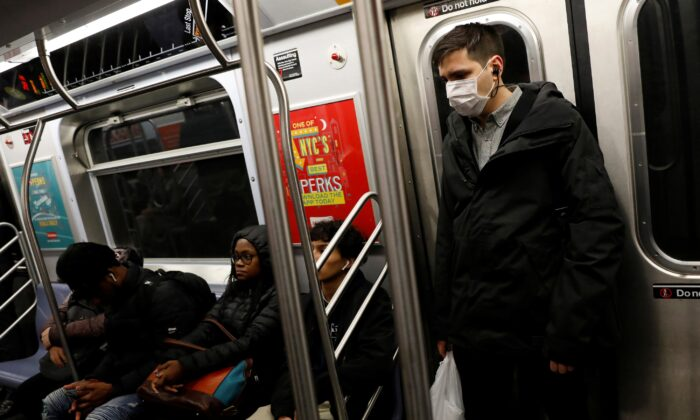 A man in a face mask rides the subway in Manhattan, New York City, after further cases of coronavirus were confirmed in New York on March 5, 2020. (Andrew Kelly/Reuters)