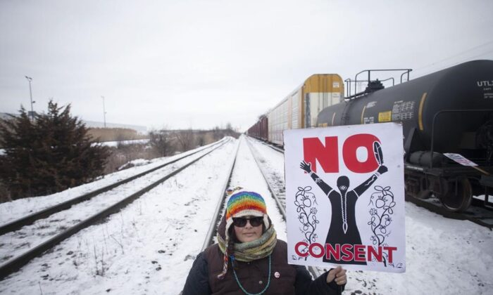 A protester holds a placard as supporters of the Wet'suwet'en hereditary chiefs demonstrate at Macmillan Yard in Toronto, on Feb. 15, 2020.Chris Young / The Canadian Press)