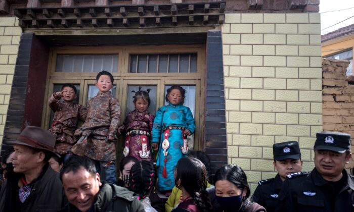 Children in traditional Tibetan clothes and police watching passing Tibetan Buddhist monks during a ceremony for Monlam, otherwise known as the Great Prayer Festival of Losar, the Tibetan New Year, at the Rongwo Monastery, in Tongren County, Huangnan Tibetan Autonomous Prefecture, on the Qinghai-Tibet plateau, on Mar. 1, 2018.  (Johannes Eisele/AFP via Getty Images)