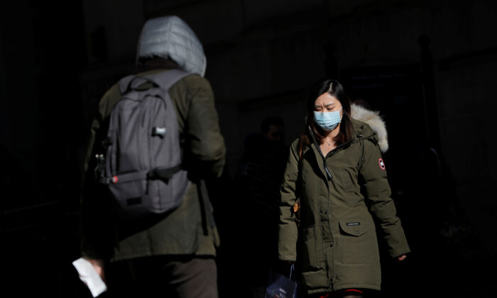 A woman in a face mask walks in the downtown area of Manhattan, New York City, after further cases of the new coronavirus were confirmed in New York on March 5, 2020. (Andrew Kelly/Reuters)