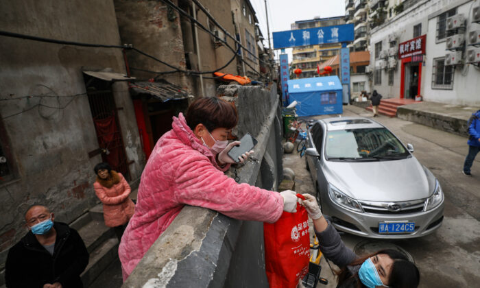 A resident (center L) receives a bag of food over a wall in Wuhan in China's central Hubei province on March 3, 2020. (STR/AFP via Getty Images)
