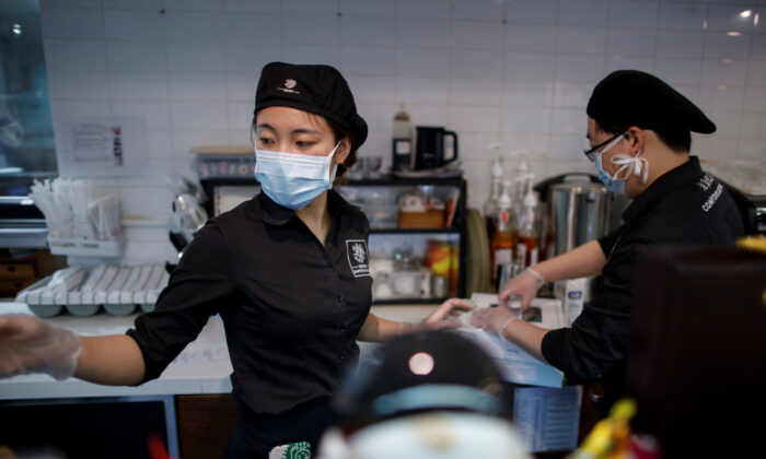 Staff members wearing masks work at a cafe of the French bakery Comptoirs de France in Beijing as the country is hit by an outbreak of the novel coronavirus, in Beijing, China, on Feb. 29, 2020.  (Thomas Peter/Reuters)